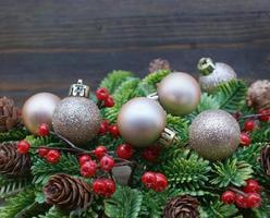 Weihnachtshintergrund mit Kugeln und Kranz gegen Holzhintergrund