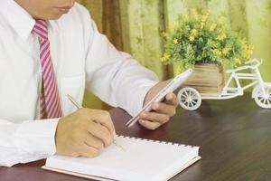 Geschäftsmann, der auf Notizbuch schreibt und Telefon am Arbeitsplatz betrachtet foto