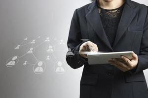 Geschäftsfrauen, die Tablette auf grauem Hintergrund verwenden foto