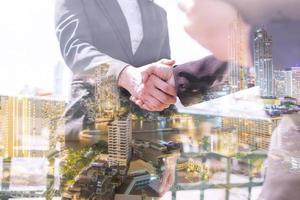 Doppelbelichtung von Geschäftsleuten, die sich die Hände schütteln foto