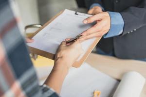 Person, die einen Vertrag auf einer Zwischenablage unterzeichnet foto