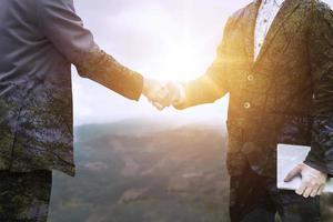 Doppelbelichtung von zwei Geschäftsleuten, die sich die Hände schütteln foto