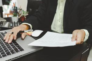 ein Geschäftsmann, der Geschäftsdokumente betrachtet und einen Stift mit einem Computer-Laptop und einem Taschenrechner am Schreibtisch hält, der von zu Hause aus arbeitet foto