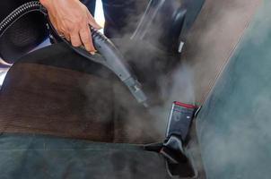 Verwenden von Dampf mit hoher Hitze, um Keime abzutöten und Autositze zu reinigen foto
