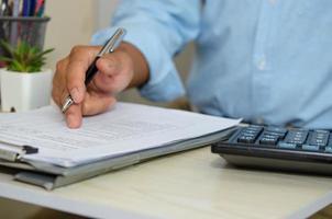ein Geschäftsmann, der Geschäftsdokumente betrachtet und einen Stift am Schreibtisch hält. Von zuhause aus arbeiten foto
