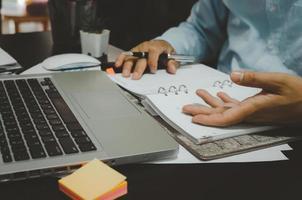 ein Geschäftsmann, der Notizen in einem Marketingstrategieplaner und in Statistiken macht, die Computerdaten betrachten foto
