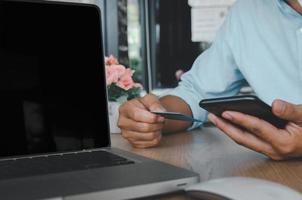 Geschäftsmann, der ein mobiles Smartphone und eine Kreditkarte mit einem Computer-Laptop auf dem Tisch verwendet foto
