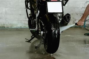 Hochdruck-Wasserpistole, die ein Motorrad in der Autowaschanlage wäscht foto