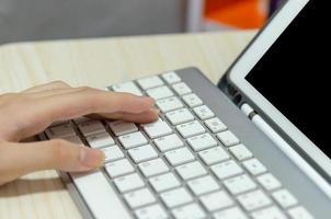 ein Mädchen, das eine Computertastatur benutzt, die online zu Hause lernt foto