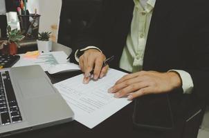 ein Geschäftsmann, der Geschäftsdokumente betrachtet und einen Stift mit einem Computer-Laptop und einem Smartphone am Schreibtisch hält, der von zu Hause aus arbeitet