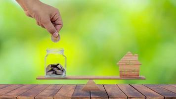 Hände, die Münzen in geldsparende Flaschen stecken und Holzhäuser auf Holzwaagen modellieren, um Sparideen für den Kauf eines neuen Hauses oder einer neuen Immobilie zu erhalten