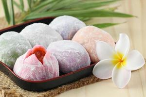 buntes japanisches Mochi-Dessert im schwarzen Tablett auf Holztisch