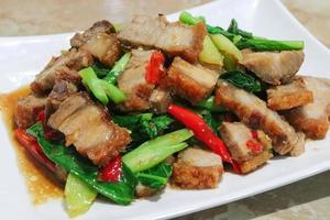 gebratener geschnittener Schweinebauch unter Rühren mit chinesischem Grünkohl auf weißem Teller braten foto