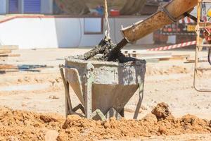 Betonmischerwagen, der flüssigen Beton in den Turmkranschaufel gießt foto