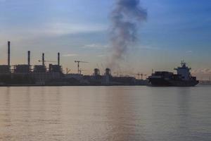 Kraftwerk und Boot bei Sonnenuntergang foto