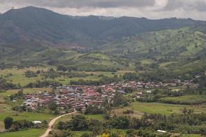 Dorf in der Nähe von bewölkten Bergen