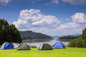 Zelte in der Nähe von Wasser und Bergen