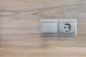elektrischer Stecker auf einem hölzernen Hintergrund