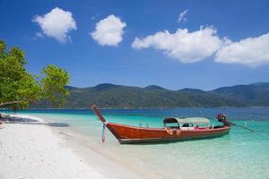 ein langes Boot an einem tropischen Strand