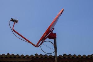 rote Satellitenschüssel auf einem Dach foto