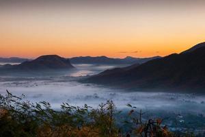 Sonnenaufgang über Bergen und Wolken