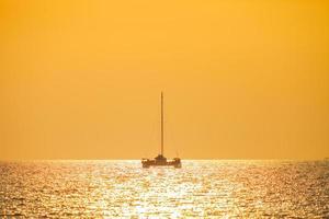 Boot auf dem Wasser mit einem orangefarbenen Sonnenuntergang