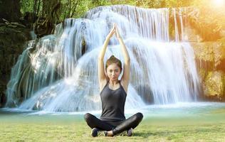 sportliche asiatische Frau, die sich mit Yoga-Pose aufwärmt