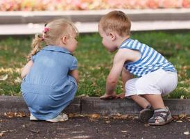 Mädchen und Junge spielen draußen foto