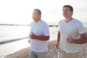 zwei Männer rennen in hellem Sonnenlicht die Küste entlang foto