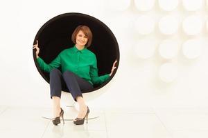 Frau sitzt auf einem kugelförmigen Stuhl foto