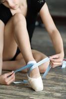 Mädchen, das ihre Ballettschuhe bindet