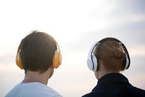 junge Leute in Kopfhörern, die draußen Musik genießen foto