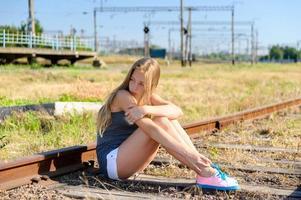 trauriges Mädchen, das auf einer Eisenbahnstrecke sitzt foto