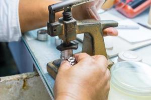 älterer Uhrmacher, der eine alte Uhr repariert foto