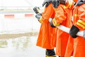 Feuerwehrleute mit Feuerlöscher und Wasser aus dem Schlauch
