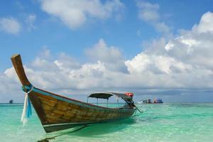 langes Boot schwimmt am tropischen Strand