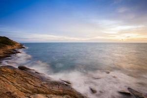 Langzeitbelichtung der Meereswellen bei Sonnenuntergang foto