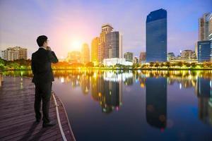 Geschäftsmann, der die Stadt auf Sonnenaufgang betrachtet foto