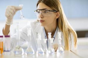 Ärztin oder wissenschaftliche Forscherin, die Flaschen mit Lösungen in einem Labor betrachtet foto