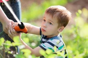 kleiner Junge spielt mit einem Schlauch