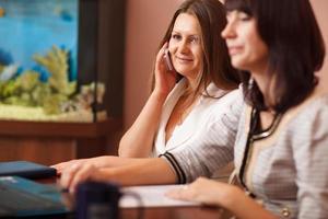 Frau spricht auf ihrem Handy in einer Besprechung