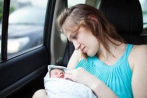 Mutter mit Neugeborenem im Auto foto