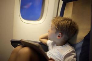 Junge im Flugzeug schaut aus dem Fenster foto