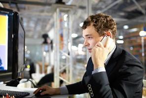 Mann arbeitet und spricht am Telefon.
