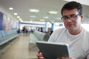Mann, der auf einer Tafel liest, während er am Flughafen wartet foto