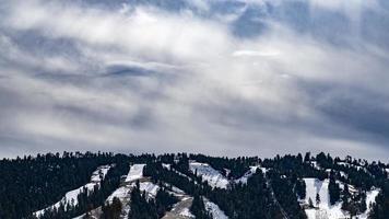 Skipisten mit Kiefern in Big Bear, Kalifornien an einem wolkigen und sonnigen Tag foto