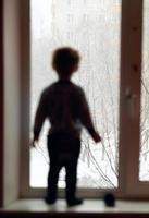 Silhouette eines Jungen in der Nähe eines Fensters foto
