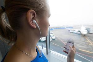 Frau, die Musik am Fenster am Flughafen hört