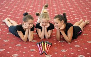 Drei Mädchen auf dem Boden betrachten Gymnastikstöcke