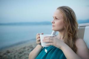 Frau, die eine Tasse Tee am Strand genießt